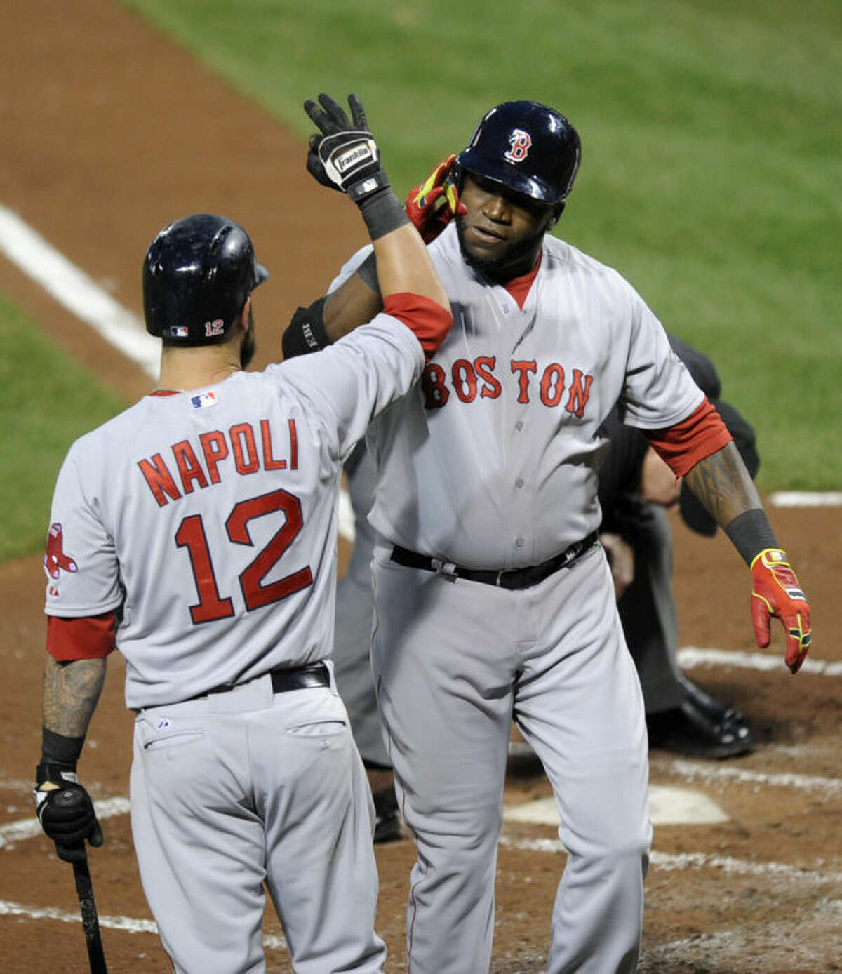 Boston Red Sox designated hitter David Ortiz, right, celebrates his two-run home run with Mike Napoli (12) during the third inning of a baseball game against the Baltimore Orioles, Wednesday, April 2, 2014, in Baltimore. (AP Photo/Nick Wass)