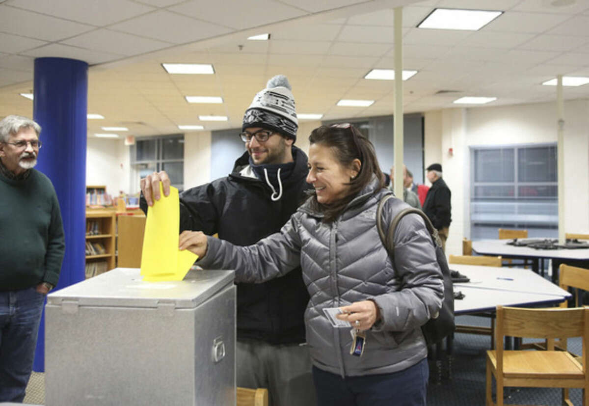 Hour photos/Danielle Calloway Above, Toni Parlanti and her son, Mike, vote for the Democrats competing for 11 District A seats on the Norwalk Democratic Town Committee during caucus Wednesday at Kendall School. Below, Hazel Lepotsky casts her vote.