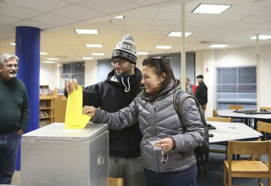 Hour photos/Danielle CallowayAbove, Toni Parlanti and her son, Mike, vote for the Democrats competing for 11 District A seats on the Norwalk Democratic Town Committee during caucus Wednesday at Kendall School. Below, Hazel Lepotsky casts her vote.
