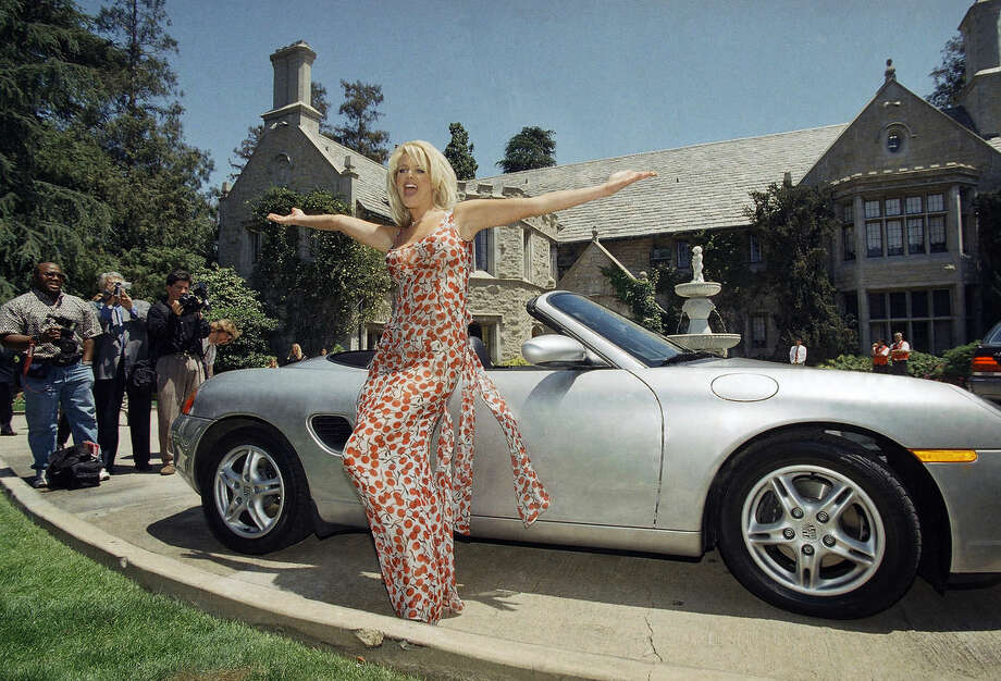 File - In this May 1, 1997, file photo, Victoria Silvstedt poses with her brand new Porsche in front of the Playboy Mansion in Beverly Hills, Calif. The Playboy Mansion is up for sale but longtime resident Hugh Heffner wants to stay put. Playboy Enterprise announced the West Los Angeles estate, the backdrop of many film shoots and wild parties, was listed on Monday, Jan. 11, 2016, for $200 million. (AP Photo/Chris Pizzello, File)