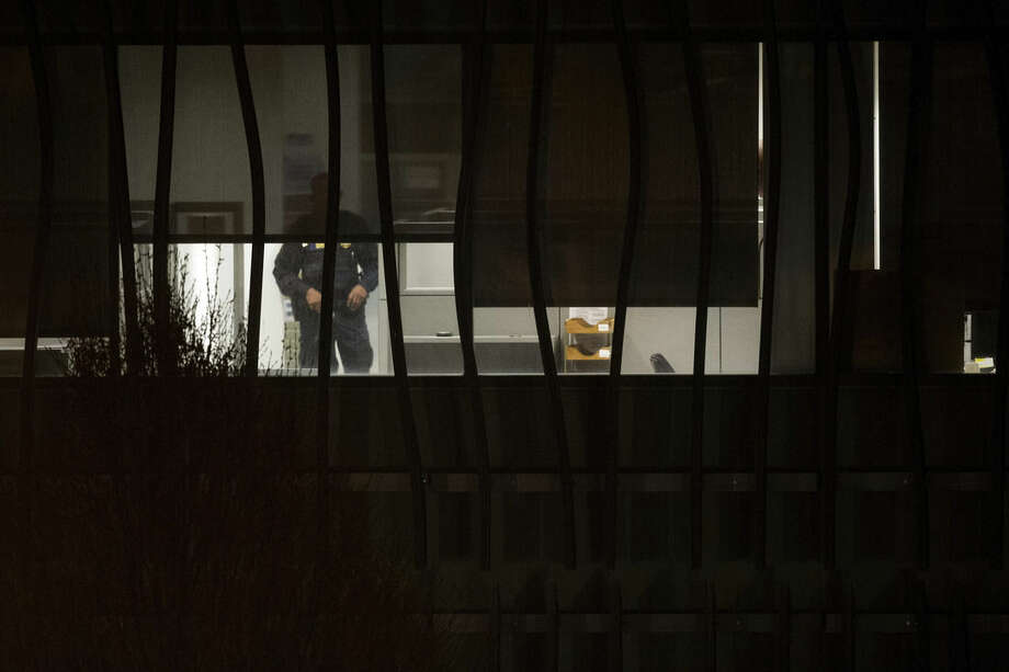 A police officer searches a building on the U.S. Census Bureau headquarters campus for an armed man who, according to a fire official, shot a security guard at a gate to the facility in Suitland, Md., Thursday, April 9, 2015. (AP Photo/Cliff Owen)
