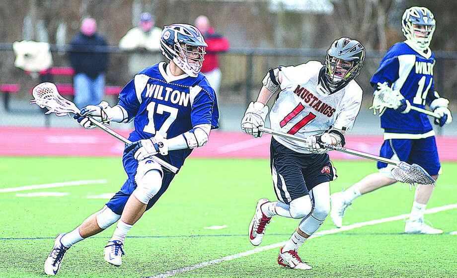 Wilton's Michael Lynch, left, drives to the goal on Fairfield Warde's Jake Fuss during Thursday's FCAIC boys lacrosse game at Tetreau-Davis Field in Fairfield. (Hour photo/John Nash)