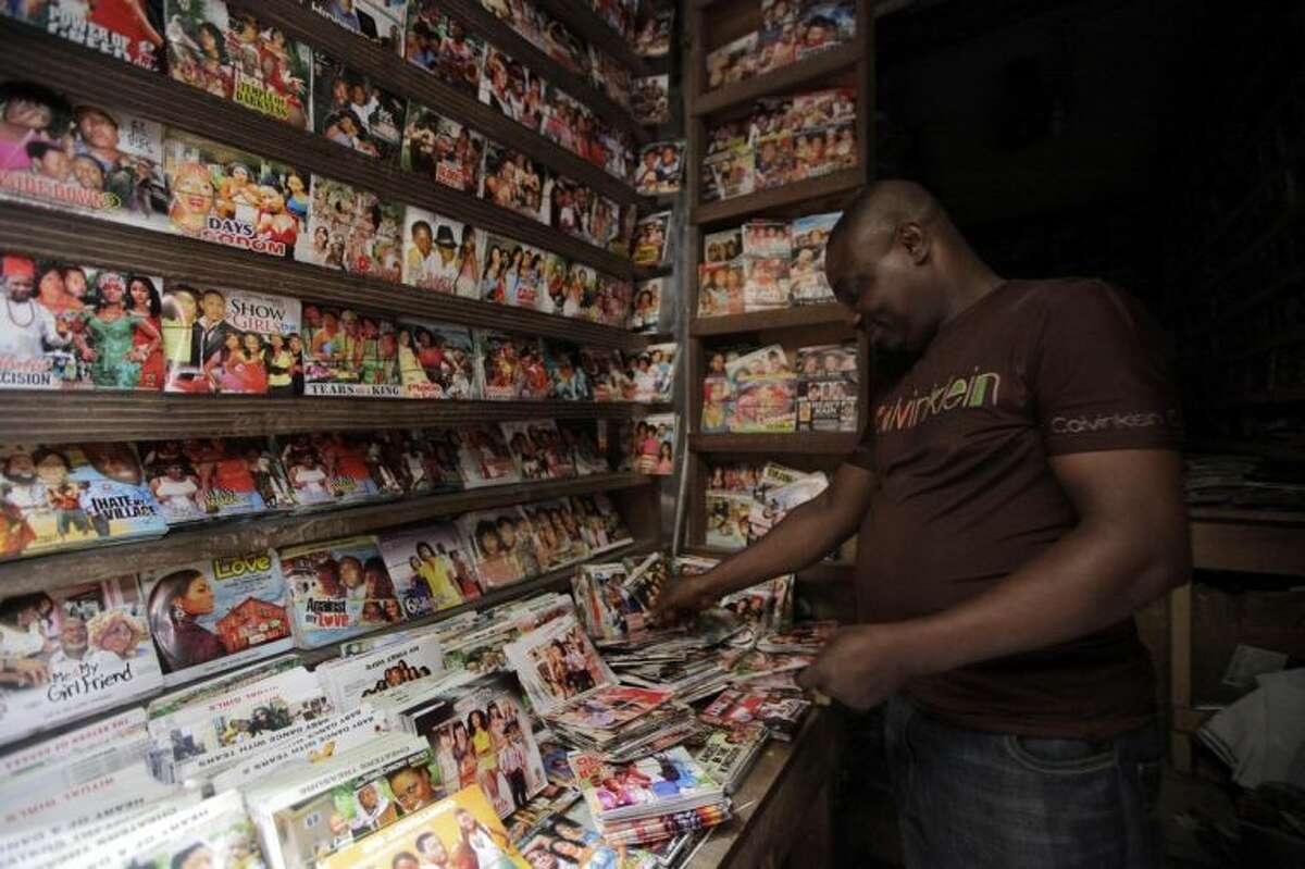 """In this photo taken Wednesday, Feb, 5. 2014, a man arranges Nollywood DVD's in a shop in Lagos, Nigeria. A 15-second drum roll and the title of the film, ?""""Deceptive Heart,?"""" comes crashing onto the screen in a groovy 1970s font. Less than 10 minutes into the Nollywood movie, the heart of plot is revealed: A woman has two boyfriends and doesn?'t know what to do. The story moves as quickly as the film appears to have been shot. Some scenes are shaky, with cameras clearly in need of a tripod, and musical montages are often filled with pans of the same building. Most Nollywood movies are made in less than 10 days and cost about $25,000. (AP Photo/ Sunday Alamba)"""