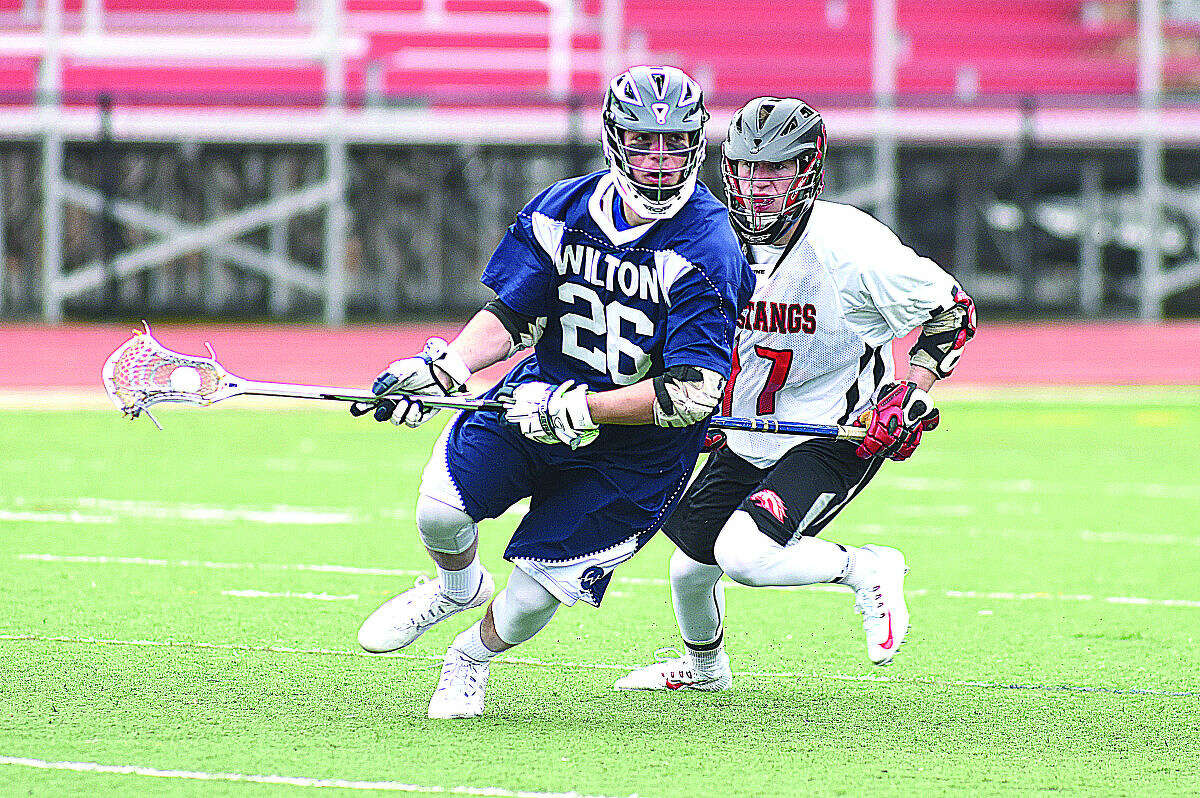 Wilton's RJ Romeo, left, races away from Fairfield Warde's RJ Bebey after winning a face off during Thursday's game at Tetreau-Davis Field in Fairfield. (Hour photo/John Nash)