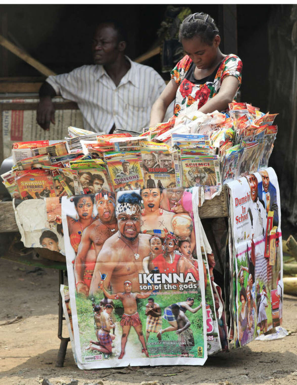 """In this photo taken Friday, Jan, 24. 2014, a woman shops for Nollywood DVD's on a street in Lagos, Nigeria. A 15-second drum roll and the title of the film, ?""""Deceptive Heart,?"""" comes crashing onto the screen in a groovy 1970s font. Less than 10 minutes into the Nollywood movie, the heart of plot is revealed: A woman has two boyfriends and doesn?'t know what to do. The story moves as quickly as the film appears to have been shot. Some scenes are shaky, with cameras clearly in need of a tripod, and musical montages are often filled with pans of the same building. Most Nollywood movies are made in less than 10 days and cost about $25,000. (AP Photo/ Sunday Alamba)"""