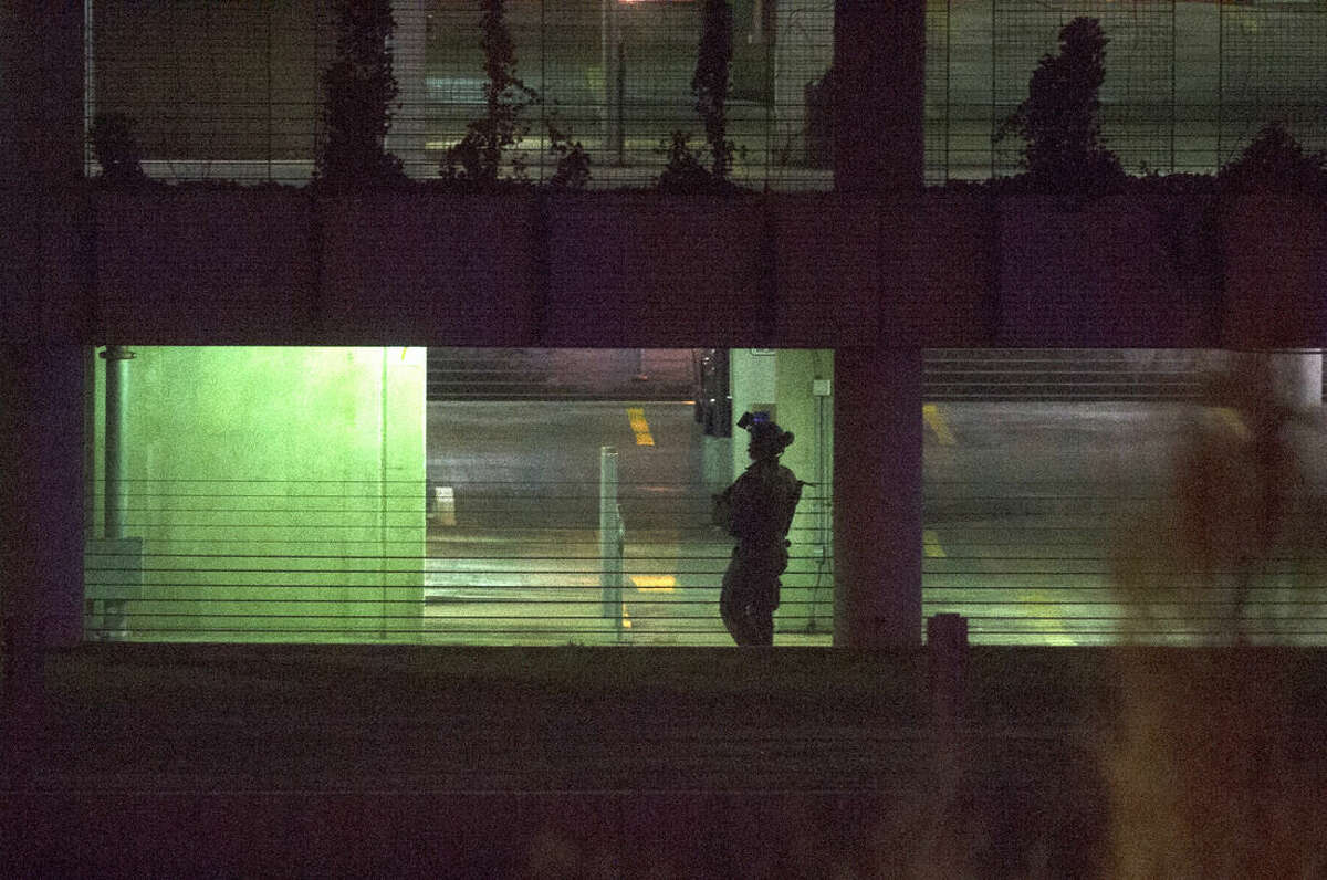 Police search a parking garage on the U.S. Census Bureau headquarters campus for an armed man who, according to a fire official, shot a security guard at a gate to the facility in Suitland, Md., Thursday, April 9, 2015. (AP Photo/Cliff Owen)
