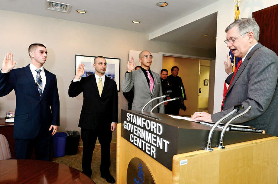 Hour photo / Erik Trautmann New Stamford police officers Luis Davila, Peter Kalmanides and Donald Chen are sworn in by Stamford Mayor David Martin Thursday morning at the Stamford Government Center.