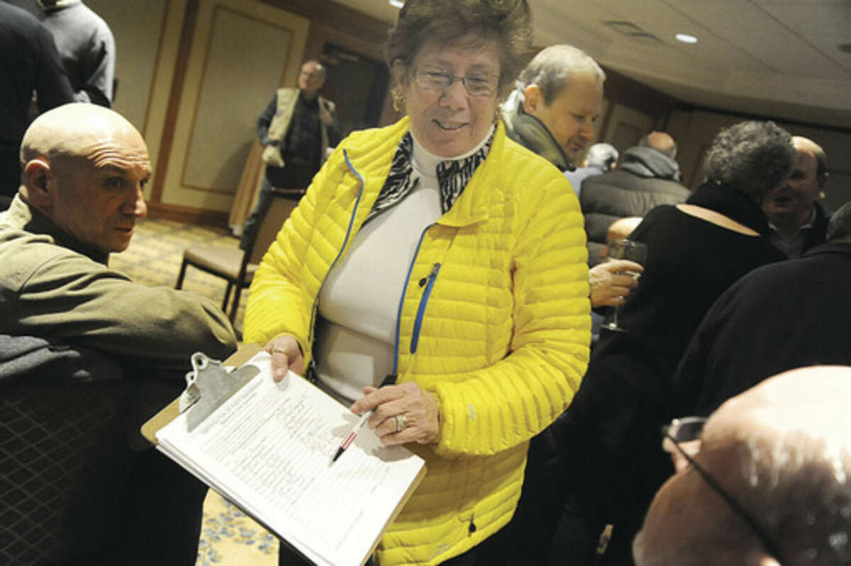 Hour photo/Matthew Vinci Karen Doyle Lyons, Registrar of Voters and District A Republican, has candidates that have party endorsement sign a certification sheet on Monday at the Republican Town Committee's caucus to nominate its 100 members at the Norwalk Inn and Conference Center.