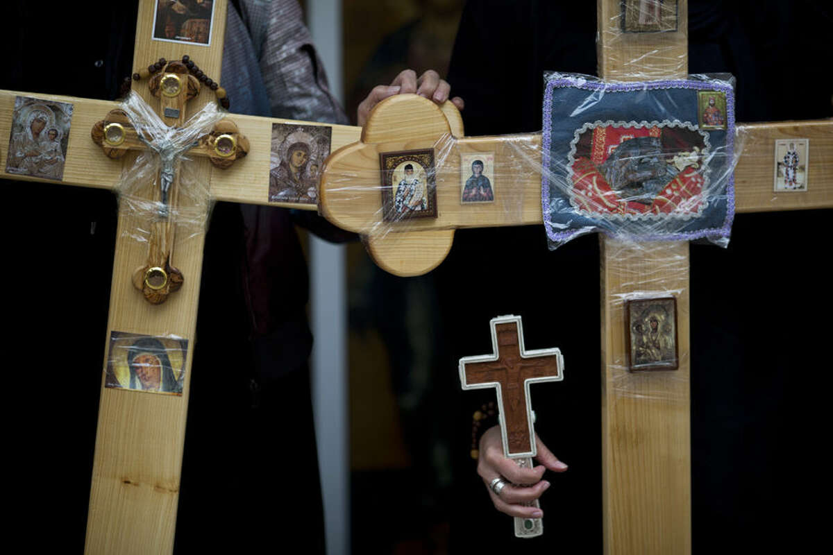 Orthodox worshippers hold crosses as they wait to walk along the Via Dolorosa towards the Church of the Holy Sepulchre, traditionally believed by many to be the site of the crucifixion of Jesus Christ, during the Good Friday procession in Jerusalem's Old City, Friday, April 10, 2015. (AP Photo/Ariel Schalit)