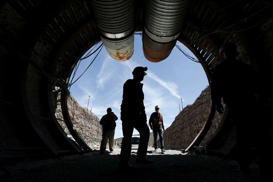 People walk into the south portal of Yucca Mountain during a congressional tour Thursday, April 9, 2015, near Mercury, Nev. Several members of Congress toured the proposed radioactive waste dump 90 miles northwest of Las Vegas. (AP Photo/John Locher)