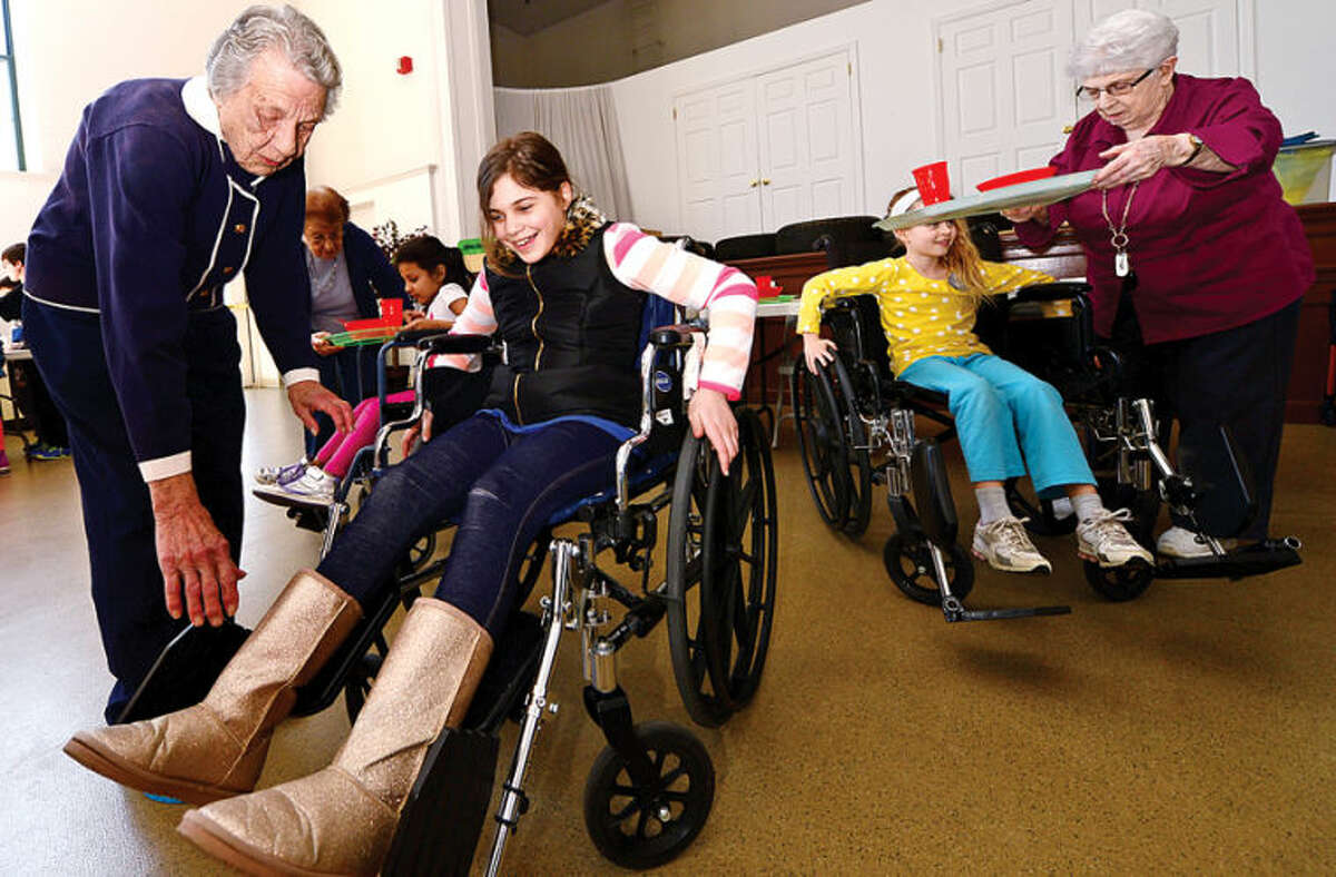 """Hour photo / Erik Trautmann Barbra Dunlap helps 4th grader Brenna Dominick into a wheelchair as students from Marvin Elementary School visit The Marvin senior residence and experience what it is like to have disabilities related to aging. During the annual event students rotate through several """"stations"""" managed by senior residents of The Marvin and they experience some of the physical and sensory challenges of aging."""