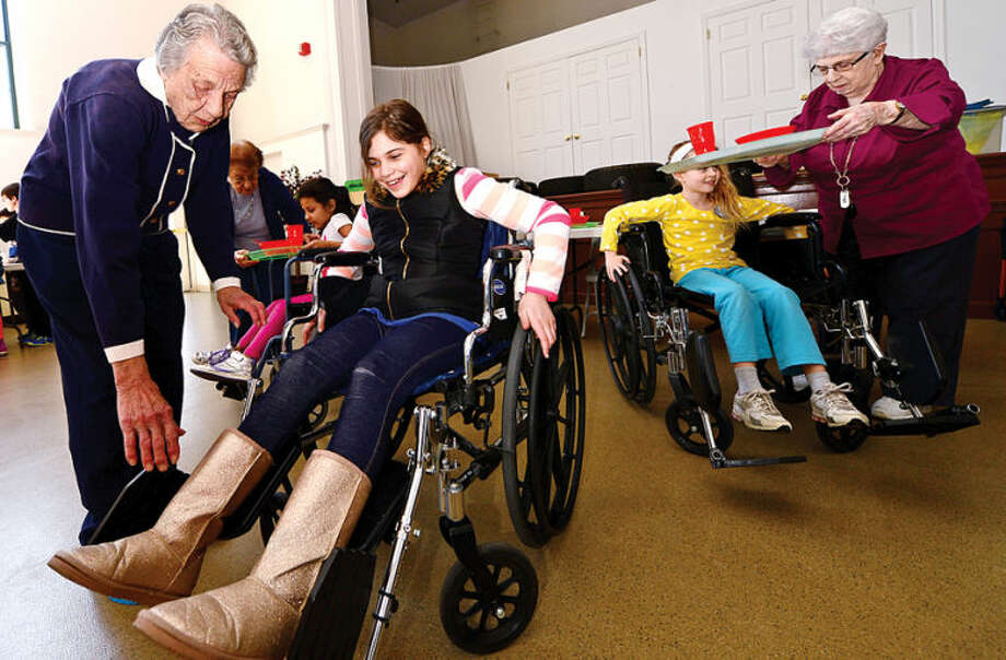 "Hour photo / Erik Trautmann Barbra Dunlap helps 4th grader Brenna Dominick into a wheelchair as students from Marvin Elementary School visit The Marvin senior residence and experience what it is like to have disabilities related to aging. During the annual event students rotate through several ""stations"" managed by senior residents of The Marvin and they experience some of the physical and sensory challenges of aging."