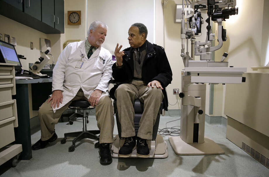 In this March 12, 2015 photo, optometrist Paul Archambault, left, talks with U.S. Army veteran Kenneth Chavis during a glaucoma examination at the Fayetteville Veterans Affairs Medical Center in Fayetteville, N.C. (AP Photo/Patrick Semansky)