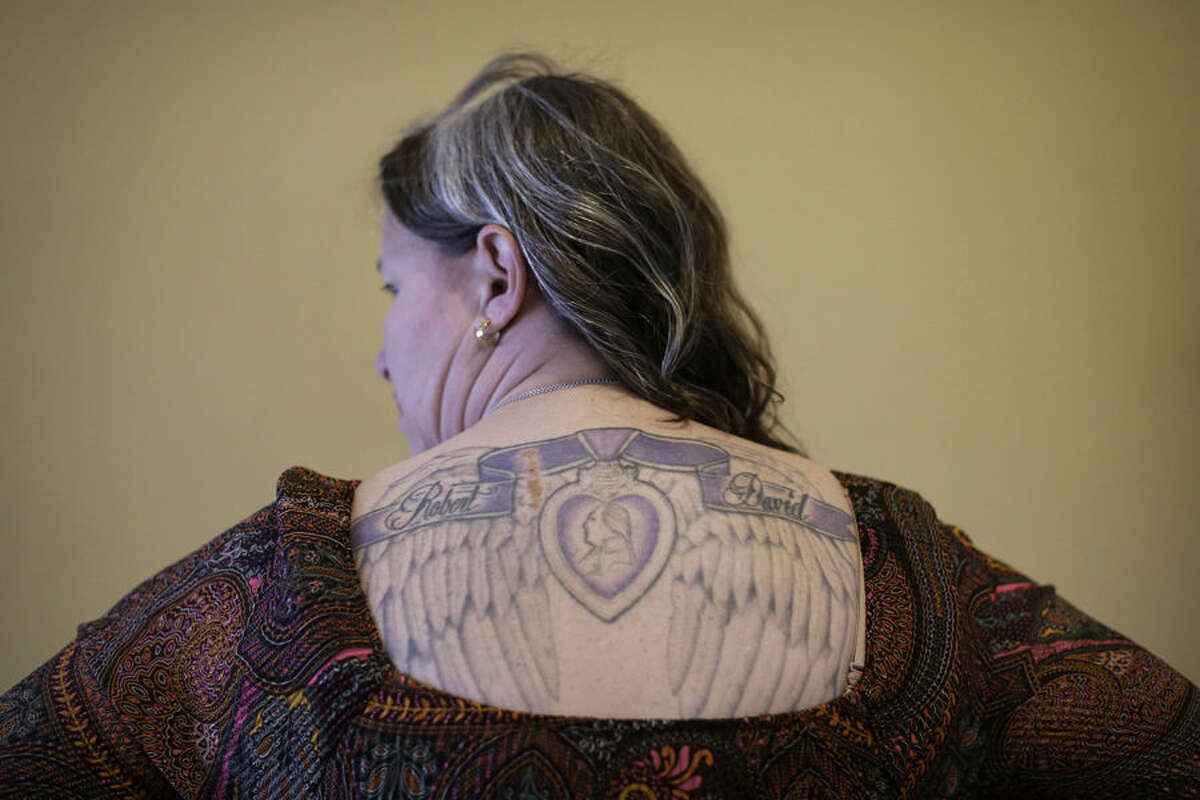 """In this March 13, 2015 photo, U.S. Marine Corps veteran Rosie Noel displays a tattoo depicting her sons' names and a Purple Heart that she was awarded, in her home in Sneads Ferry, N.C. After an abrupt cancellation of an already postponed appointment at the VA hospital in Fayetteville, Noel said she was so enraged. """"I served my country. I'm combat wounded. And to be treated like I'm nothing is unconscionable,"""" she said. (AP Photo/Patrick Semansky)"""