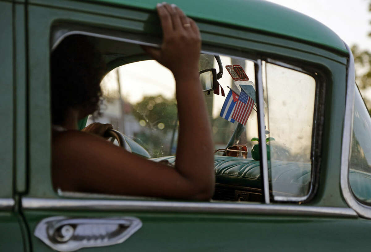 A woman sits in a private collective taxi, decorated with Cuban and U.S. flags, in Havana, Cuba, Thursday, April 9 2015. President Barack Obama signaled Thursday he will soon remove Cuba from the U.S. list of state sponsors of terrorism, boosting hopes for improved ties as he prepared for a historic encounter with Cuban President Raul Castro during the Summit of the Americas taking place in Panama. (AP Photo/Desmond Boylan)
