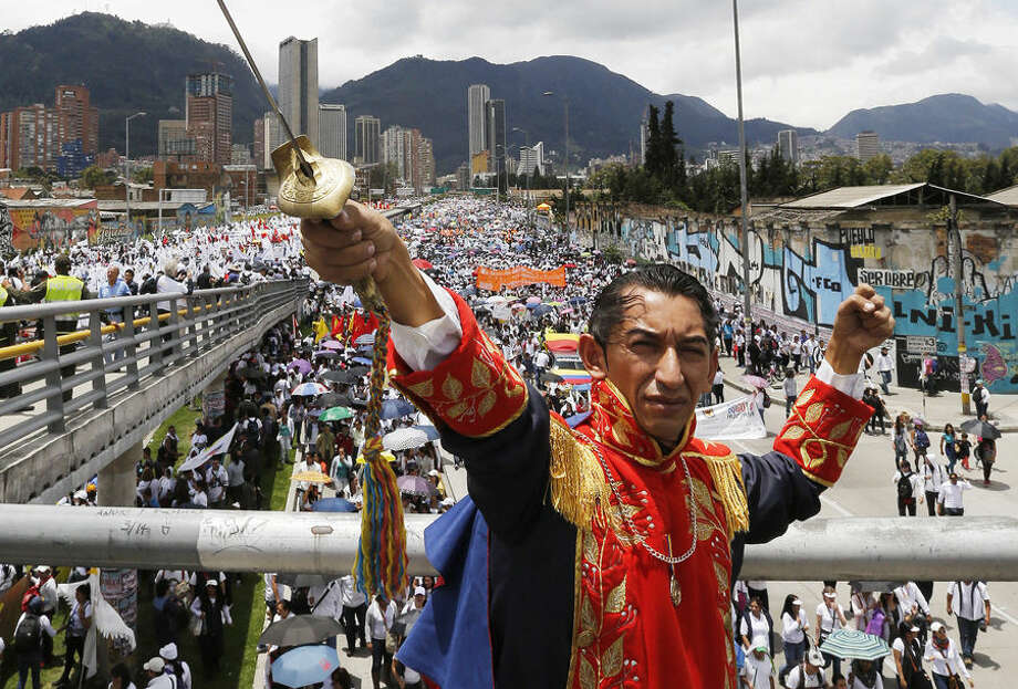 A man dressed as independence hero Simon Bolivar attends a march for peace on the National Day of Memory and Solidarity with Victims of the Armed Conflict, in Bogota, Colombia, Thursday, April 9, 2015. Thousands of marchers waved white flags and paraded through cities across the country Thursday to support peace talks between the government and guerrillas, and pay tribute to victims of the nation's armed conflict. (AP Photo/Fernando Vergara)