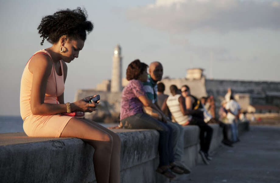 "In this March 11, 2014 photo, a woman uses her cellphone as she sits on the Malecon in Havana, Cuba. The U.S. Agency for International Development masterminded the creation of a ""Cuban Twitter,"" a communications network designed to undermine the communist government in Cuba, built with secret shell companies and financed through foreign banks, The Associated Press has learned. The project, which lasted more than two years and drew tens of thousands of subscribers, sought to evade Cuba's stranglehold on the Internet with a primitive social media platform. (AP Photo/Franklin Reyes)"