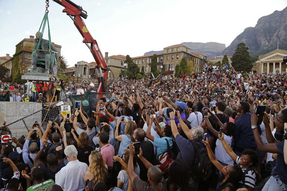 Students surround the decades old bronze statue of British colonialist Cecil John Rhodes, top left, as the statue is removed from the campus at the Cape Town University, Cape Town, South Africa, Thursday, April 9, 2015, responding to student protests describing it as symbolic of slow racial change on campus. Cecil Rhodes lived from 1853 until 1902, he was a businessman and politician in South Africa and was a fervent believer in British colonial rule. (AP Photo/Schalk van Zuydam)
