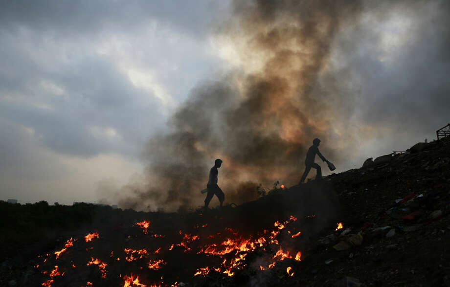 Impoverished Indians walk next to burning trash after relieving themselves in the open at Dharavi, one of the world's largest slums, in Mumbai, India, Thursday, April 9, 2015. Air pollution kills millions of people every year, including more than 627,000 in India, according to the World Health Organization. The WHO puts 13 Indian cities in the world's 20 most polluted. (AP Photo/Rafiq Maqbool)