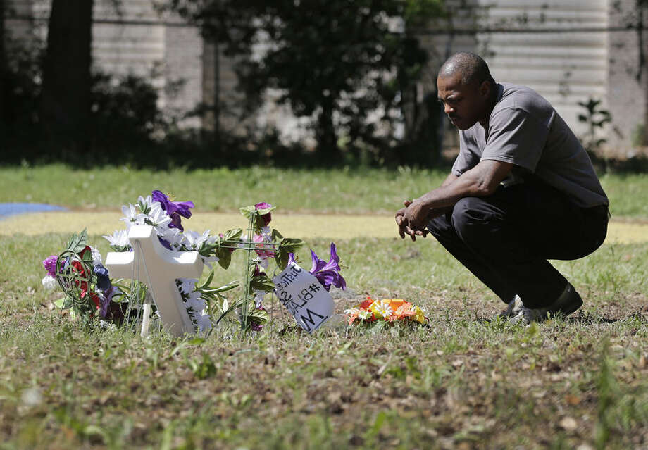 Terence Wright, of North Charleston, S.C., pays his respects at the scene where Walter Scott was killed by a North Charleston police officer Saturday, after a traffic stop in North Charleston, S.C., Thursday, April 9, 2015. Wright is a friend of the family. The officer, Michael Thomas Slager, has been fired and charged with murder. (AP Photo/Chuck Burton)