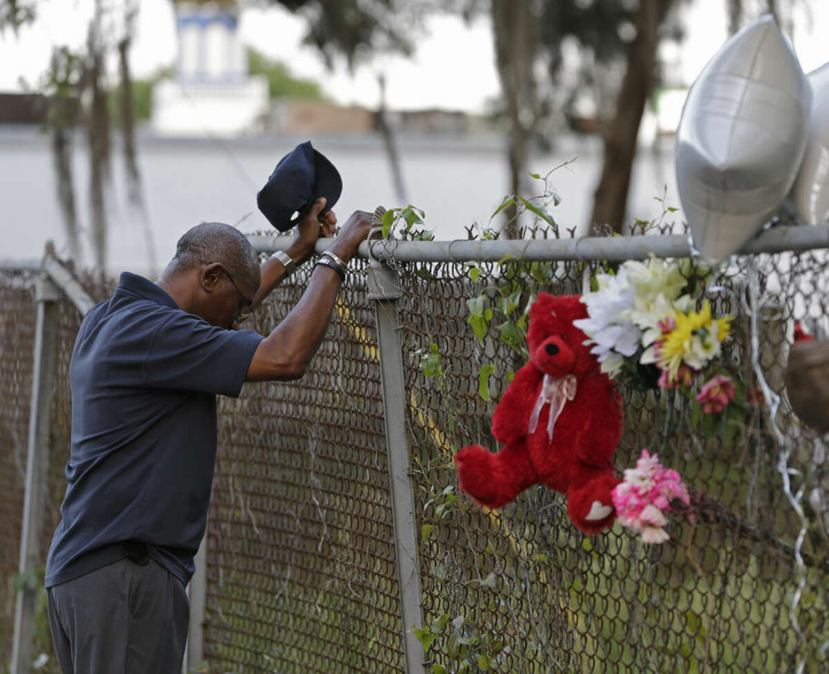 Jerome Flood, of James Island, S.C., pauses for a moment of silence at the scene the killing of Walter Scott by a North Charleston police officer Saturday after a traffic stop in North Charleston, S.C., Friday, April 10, 2015. Scott was best man at Flood's wedding and Flood said he wanted to see where it happened. The officer, Michael Thomas Slager, has been fired and charged with murder. (AP Photo/Chuck Burton)