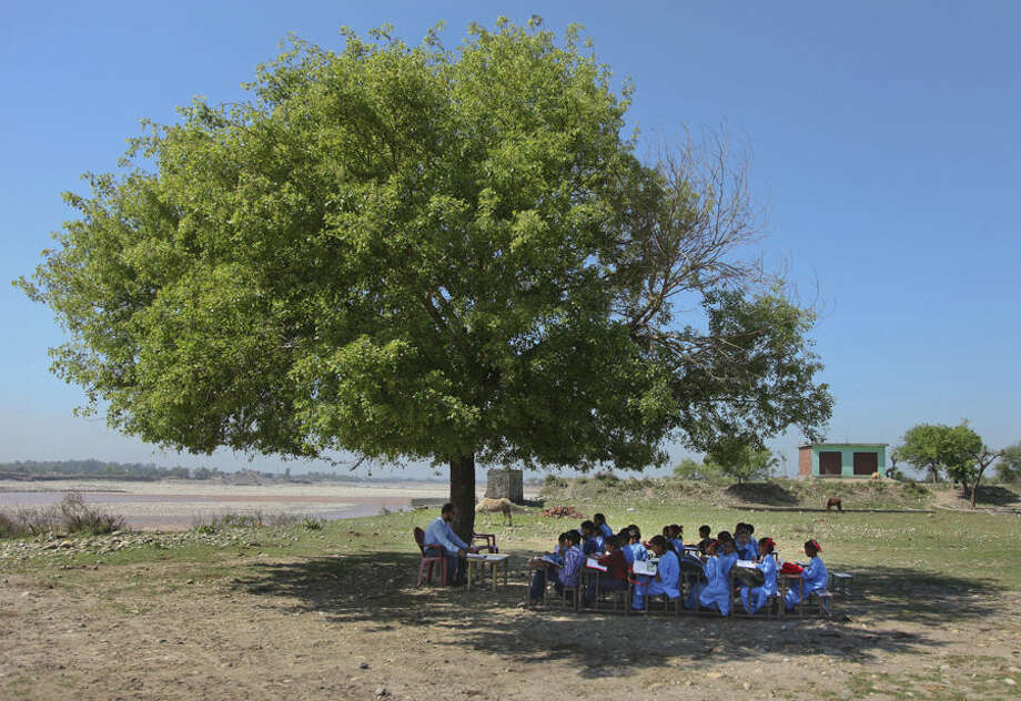 Young Indian children study in the shade of a tree at their government-run school on the outskirts of Jammu, India, Thursday, April 9, 2015. According to the UNESCO Education for All Global Monitoring Report 2015, two out of three countries where lower secondary education was not compulsory in 2000 had changed their legislation by 2012, including India, Indonesia, Nigeria and Pakistan. According to the report, rural India saw substantial improvement in nearly all aspects of school facilities and infrastructure between 2003 and 2010. (AP Photo/Channi Anand)