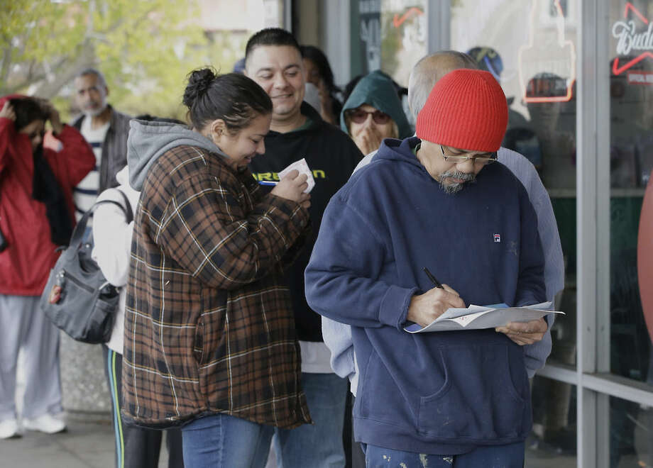 Leo Lopez, right, picks his numbers on a lottery form as he waits in line to purchase Powerball lottery tickets at Lichine's Liquor store, Wednesday, Jan. 13, 2016, in Sacramento, Calif. The Powerball jackpot for Wednesday night's drawing is at least $1.5 billion, the largest lottery jackpot in the world. (AP Photo/Rich Pedroncelli)