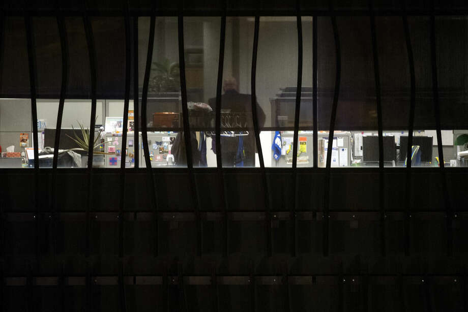 A person is seen in a building on the U.S. Census Bureau headquarters campus as police search for an armed man who, according to a fire official, shot a security guard at a gate to the facility in Suitland, Md., Thursday, April 9, 2015. (AP Photo/Cliff Owen)