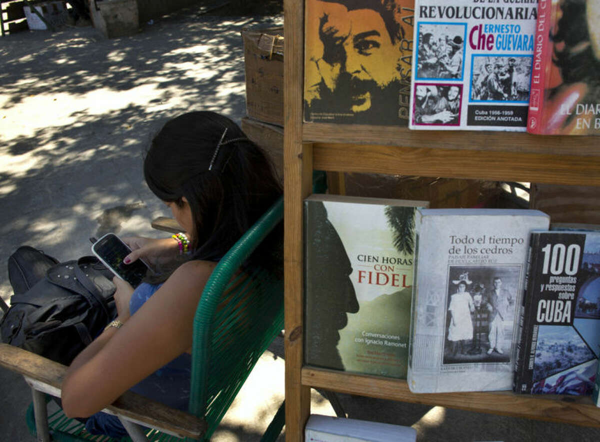 """A book street vendor passes the time on her smart phone as she waits for customers in Havana, Cuba, Tuesday, April 1, 2014. The Obama administration secretly financed a social network in Cuba to stir political unrest and undermine the country?'s communist government according to an Associated Press investigation. The project, dubbed """"ZunZuneo,"""" slang for a Cuban hummingbird?'s tweet, lasted more than two years and drew tens of thousands of subscribers and sought to evade Cuba?'s stranglehold on the Internet with a primitive social media platform. First, the network would build a Cuban audience, mostly young people; then, the plan was to push them toward dissent. (AP Photo/Ramon Espinosa)"""