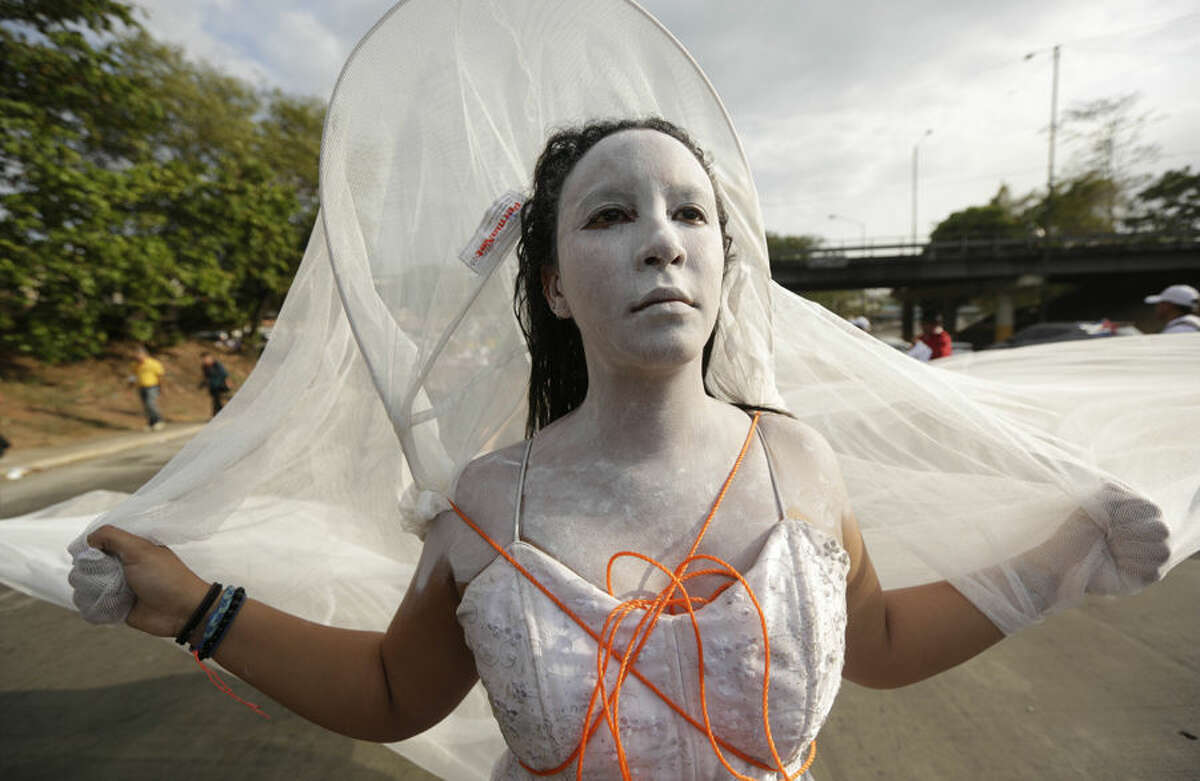 """A woman performs during a protest march against U.S. policies in Latin America, by the participants of the """"Cumbre de los Pueblos"""" or """"People's Summit"""" in Panama City, Thursday, April 9, 2015. Panama will host the Summit of the Americas on April 10-11. (AP Photo/Arnulfo Franco)"""