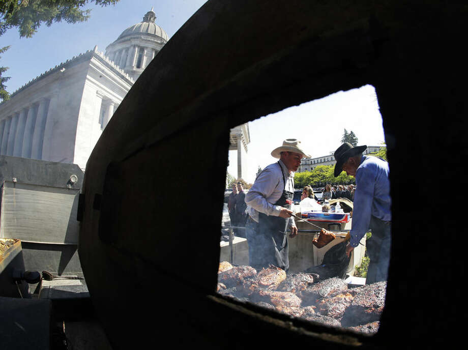 Don Blakemore, right, of Touchet, Wash., and Jack Field, of Yakima, Wash., are seen through a grill vent as they cook tri-tip beef roasts next to the Legislative Building, Thursday, April 9, 2015, at the Capitol in Olympia, Wash. Members of the Washington Cattlemen's Association and other organizations served up free beef sandwiches to visitors and Capitol workers as part of the industry's annual lobby day. (AP Photo/Ted S. Warren)
