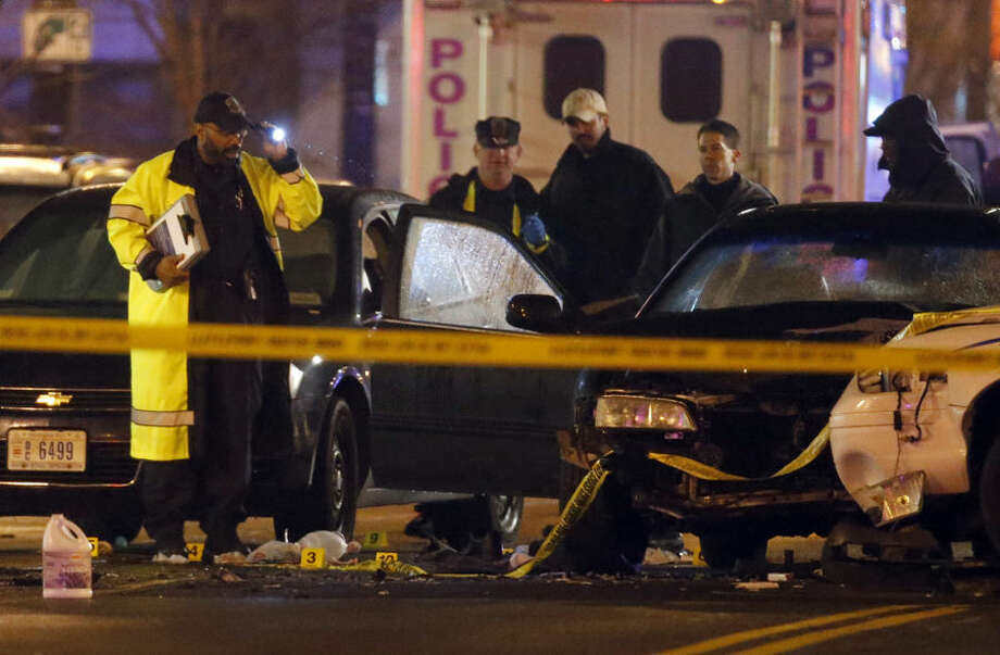 Law enforcement officers investigate the scene involving at least one wrecked DC Metro police car Thursday, April 9, 2015, in Washington. An armed man kidnapped a woman, shot a Census Bureau guard and led police on a car chase through Maryland and Washington, D.C., on Thursday before authorities cornered him in an exchange of gunfire. (AP Photo/Alex Brandon)