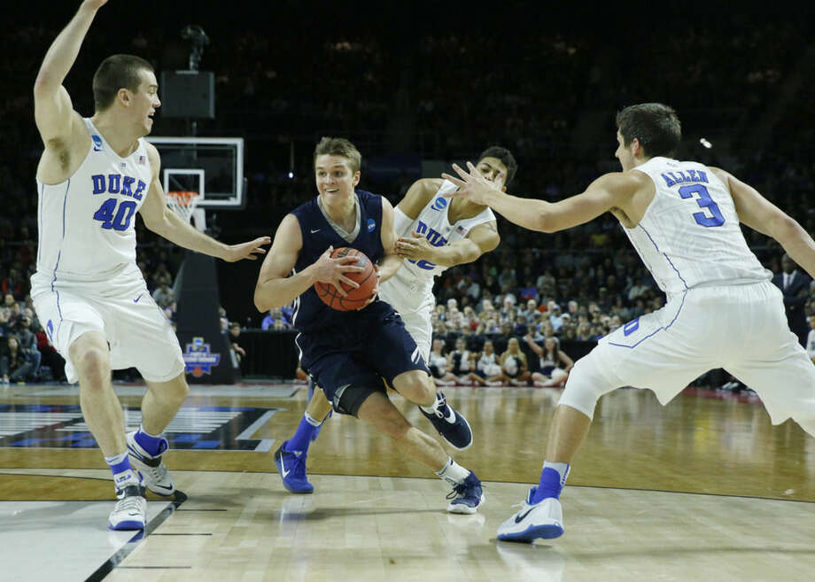 Yale's Makai Mason, center, drives between Duke's Marshall Plumlee (40) and Grayson Allen (3) during the first half in the second-round of the NCAA men's college basketball tournament in Providence, R.I., Saturday, March 19, 2016. (AP Photo/Michael Dwyer)
