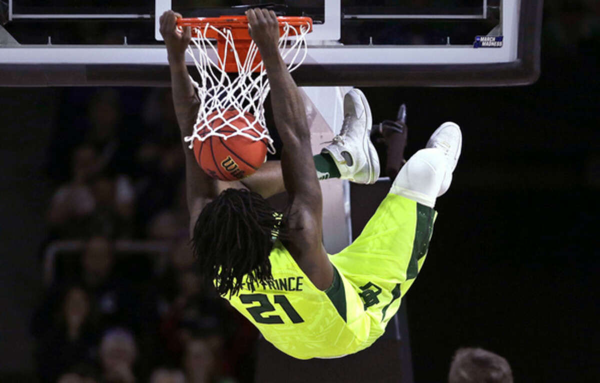 Baylor forward Taurean Prince hangs from on a dunk against Yale during the first half in the first round of the NCAA college men's basketball tournament in Providence, R.I., Thursday, March 17, 2016. Prince was charged with a technical foul on the play. (AP Photo/Charles Krupa)