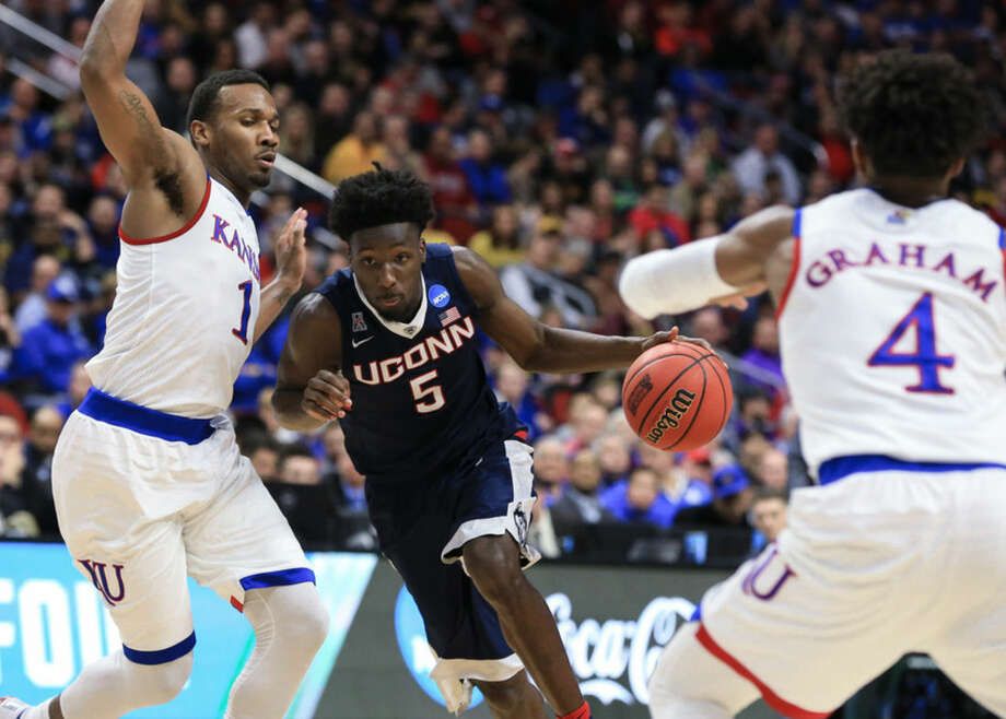 Connecticut's Daniel Hamilton (5) drives between Kansas' Wayne Selden Jr. (1) and Devonte' Graham (4) during a second-round men's college basketball game in the NCAA Tournament in Des Moines, Iowa, Saturday, March 19, 2016. (AP Photo/Nati Harnik)