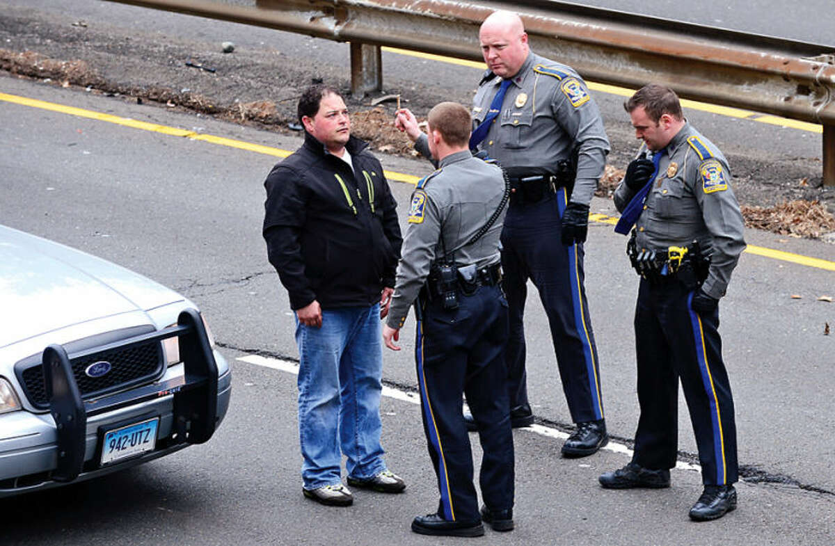 Hour photo / Erik Trautmann CT State police administer a field sobriety test on the driver of a Nissan that rolled over on the Merritt Parkway Northbound between exits 38 and 39 in a single car accident that shut down traffic in both directions.