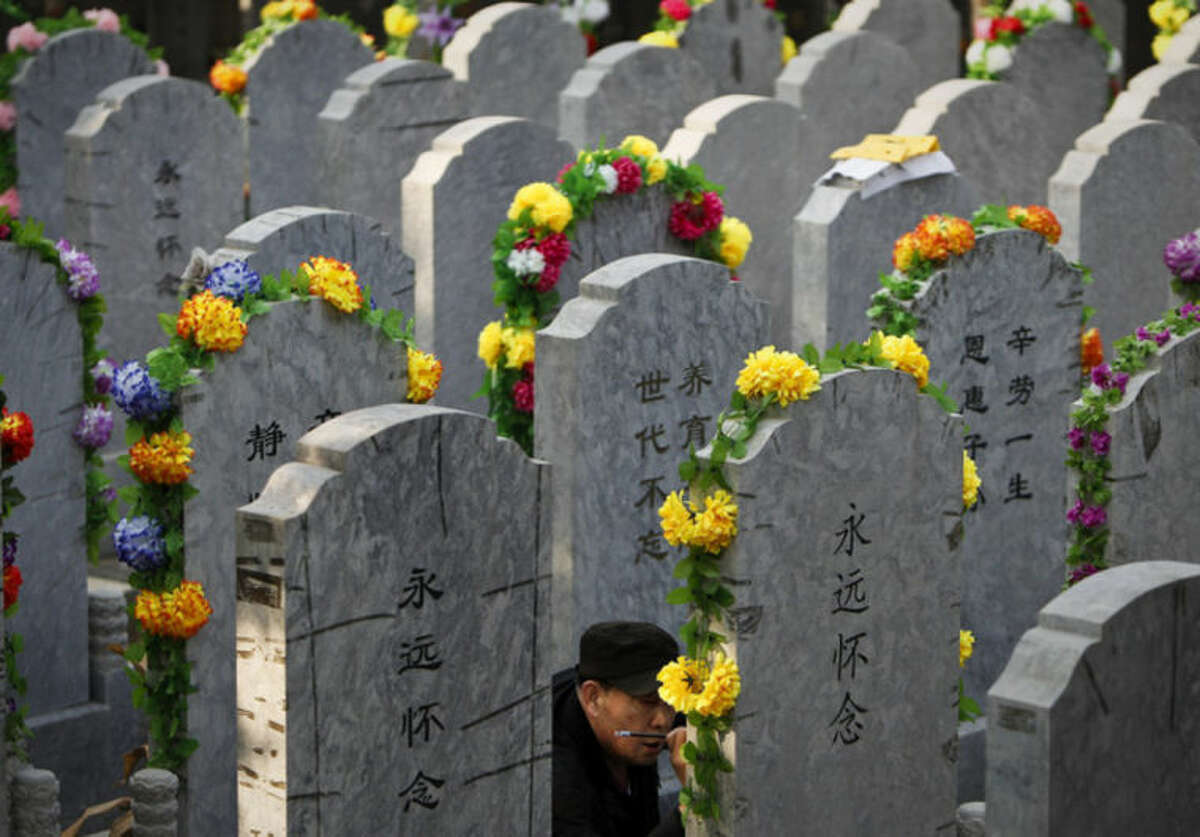 FILE - In this Tuesday, April 5, 2011 file photo, a Chinese man repaints the characters on a tomb of his deceased relative at a cemetery on the Qingming Festival in Beijing, China. On Tomb-Sweeping Day, families typically visit the ancestral burial plot to clean the graves and present offerings of fruit and burn paper money. Some set off firecrackers for good luck and to drive off evil spirits. Such traditions are strong in rural areas, though they are falling by the wayside as people migrate to the cities. (AP Photo/Andy Wong, File)