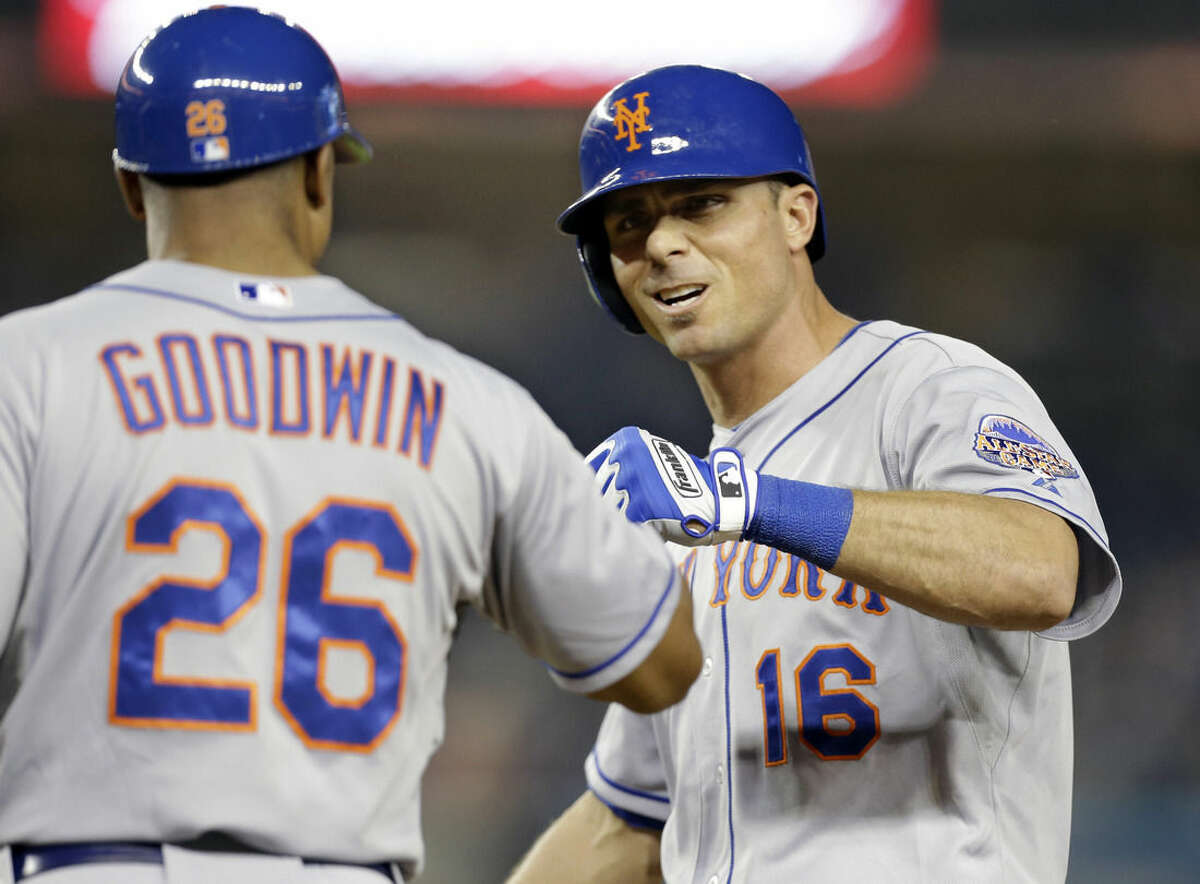 FILE - In this May 29, 2013, file photo, New York Mets first base coach Tom Goodwin (26) congratulates Mets Rick Ankiel (16) who hit a ninth-inning RBI-single in a 9-4 victory over the New York Yankees in an interleague baseball game at Yankee Stadium in New York. Ankiel was one of baseball's top pitching prospects when he broke into the majors with St. Louis in 1999. But he struggled with his control in the playoffs in 2000, throwing five wild pitches in his first postseason appearance, and was never the same pitcher again. He restarted his career as an outfielder and made it back to the majors, finishing with a .240 batting average, 76 homers and 251 RBIs in 11 seasons. Ankiel joining the Nationals organization in January to work with minor leaguers as a life skills coordinator. (AP Photo/Kathy Willens, File)