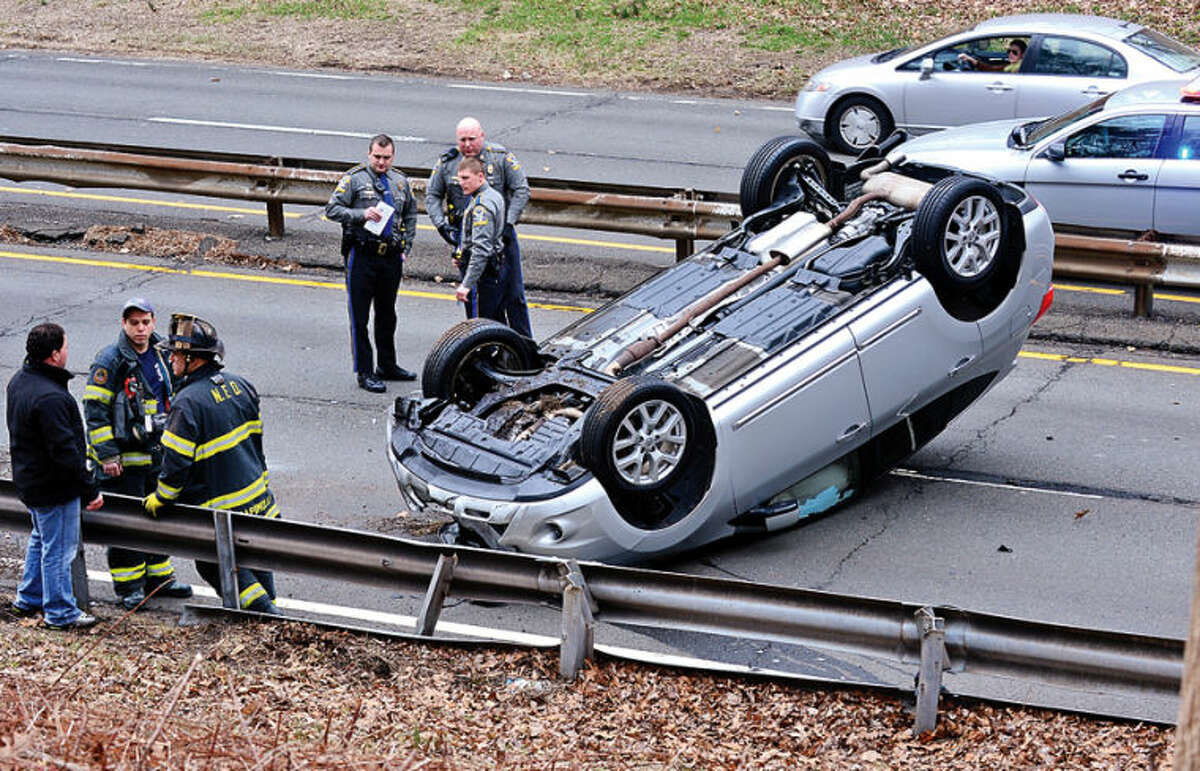 Hour photo / Erik Trautmann A Nissan rolled over on the Merritt Parkway Northbound between exits 38 and 39 in a single car accident that shut down traffic.