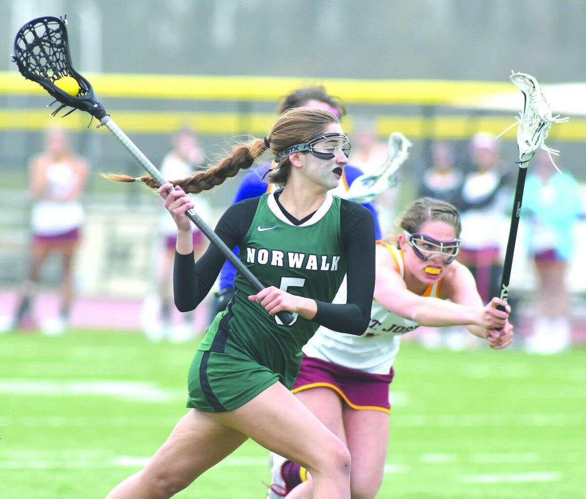 Norwalk's Hannah Froelich, left, fires off a shot during Friday's FCIAC girls lacrosse game against St. Joseph. (Hour photo/John Nash)