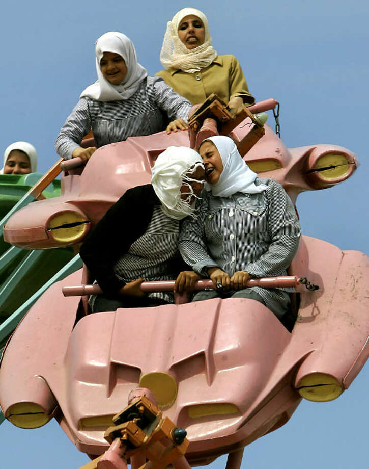 """FILE - In this Sunday, March 26, 2006 file photo, Palestinians enjoy a ride at an amusement park outside Gaza City. Anja Niedringhaus, a courageous and immensely talented Associated Press photographer who has covered everything from sports to war, was killed while covering elections in Afghanistan on Friday April 4, 2014. Niedringhaus was in a car in eastern Afghanistan with AP reporter Kathy Gannon when, according to a freelancer who was with them, an Afghan policeman approached them, yelled """"Allahu Akbar"""" _ God is Great _ and opened fire on them in the back seat with his AK-47. Niedringhaus was killed instantly and Gannon was wounded. (AP Photo/Anja Niedringhaus, File)"""