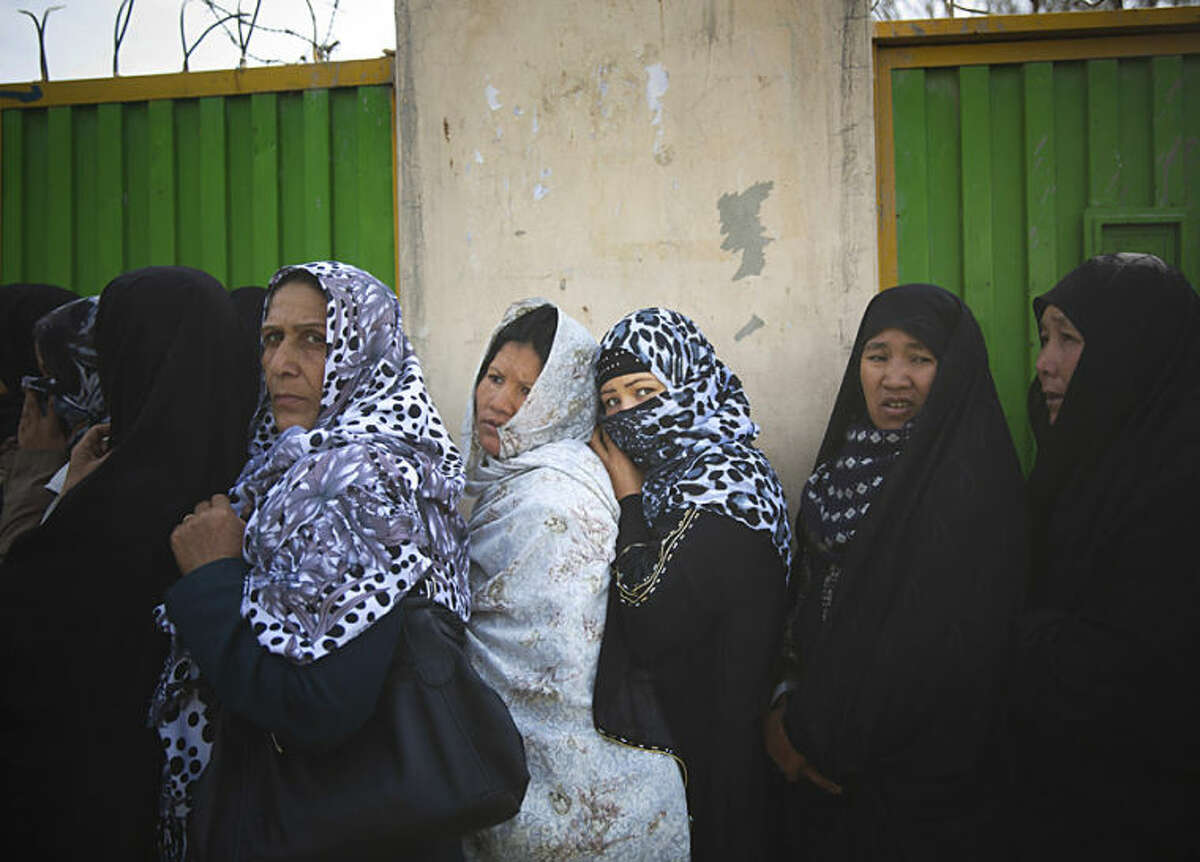 Afghan women queue outside a school to get their registration card on the last day of voter registration for the upcoming presidential elections outside a school in Kabul, Afghanistan, Tuesday, April 1, 2014. Elections will take place on April 5, 2014. (AP Photo/Anja Niedringhaus)