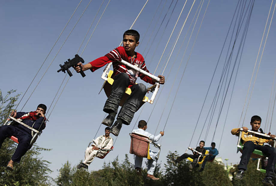 """FILE - In this Sunday, Sept. 20, 2009 file photo, an Afghan boy holds a toy gun as he enjoys a ride with others on a merry-go-round to celebrate the Eid al-Fitr festival, in Kabul, Afghanistan. Anja Niedringhaus, a courageous and immensely talented Associated Press photographer who has covered everything from sports to war, was killed while covering elections in Afghanistan on Friday April 4, 2014. Niedringhaus was in a car in eastern Afghanistan with AP reporter Kathy Gannon when, according to a freelancer who was with them, an Afghan policeman approached them, yelled """"Allahu Akbar"""" _ God is Great _ and opened fire on them in the back seat with his AK-47. Niedringhaus was killed instantly and Gannon was wounded. (AP Photo/Anja Niedringhaus, File)"""