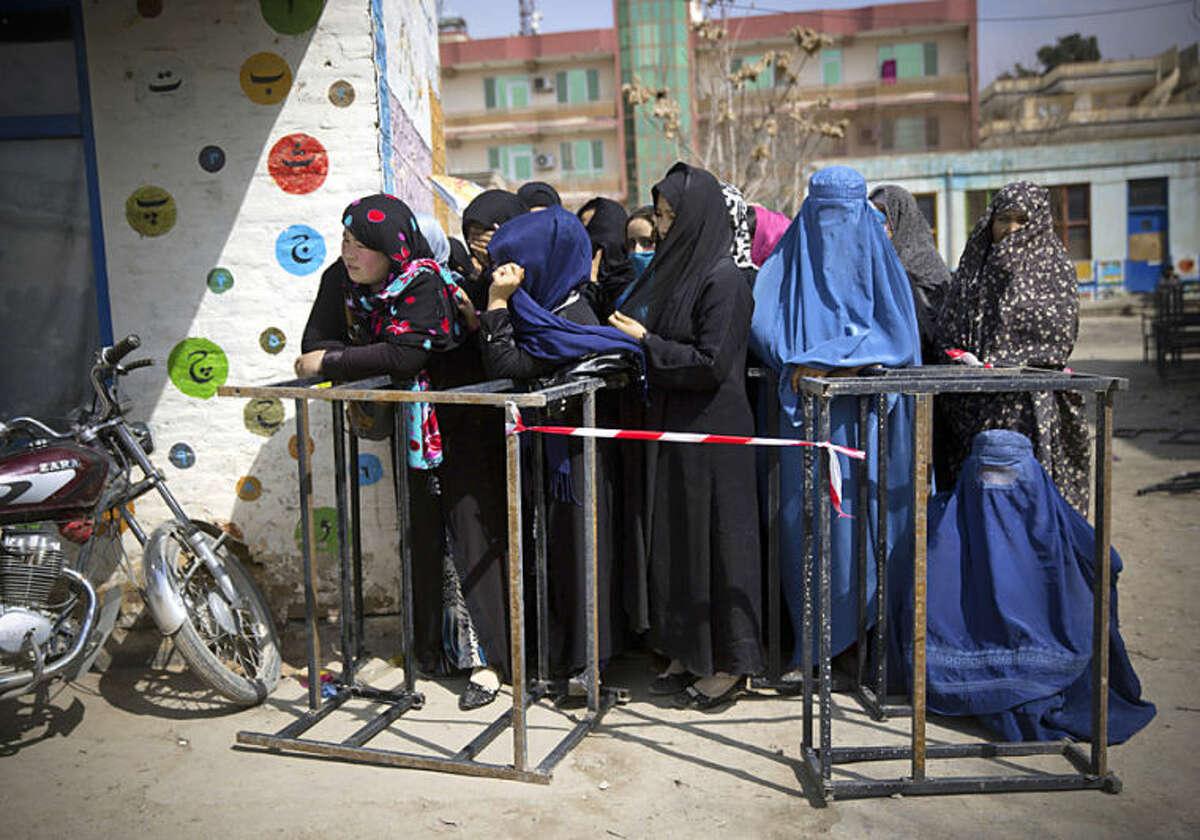 Afghan women wait to get their registration card on the last day of voter registration for the upcoming presidential elections outside a school in Kabul, Afghanistan, Tuesday, April 1, 2014. Elections will take place on April 5, 2014. (AP Photo/Anja Niedringhaus)