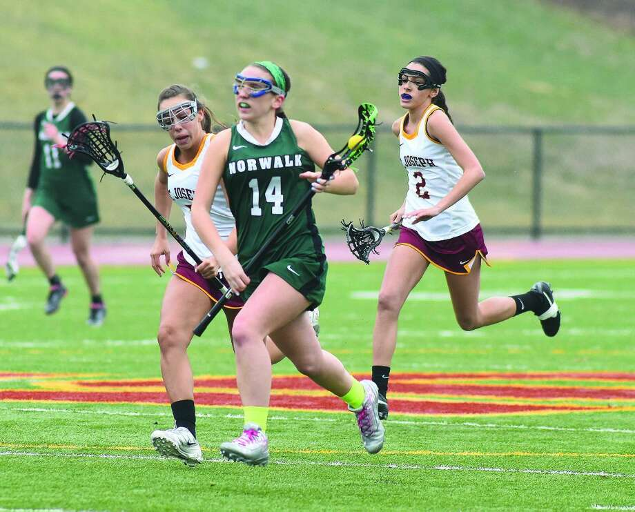 Norwalk's Kaitlin Uralowich (14) races in front of two St. Joseph players during Friday's FCIAC girls lacrosse game in Trumbull. (Hour photo/John Nash)