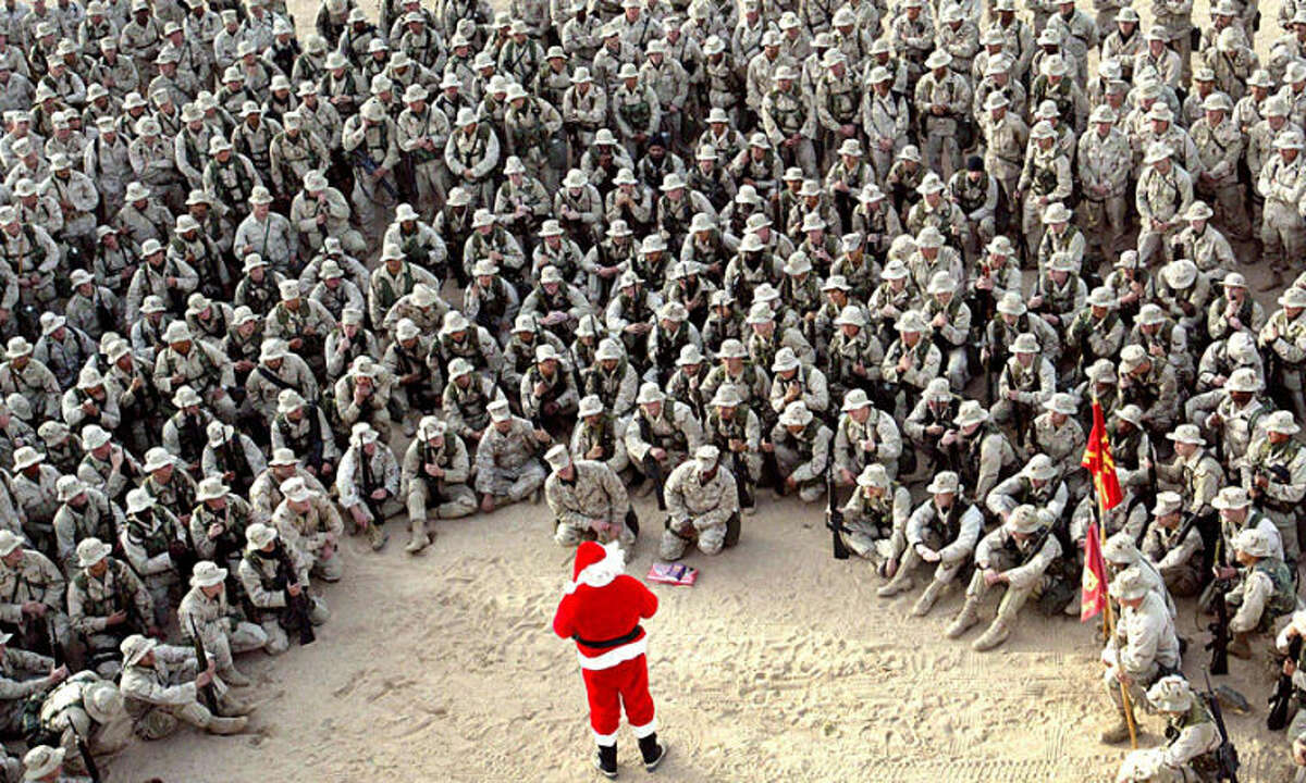 """FILE - In this Tuesday, Dec. 24, 2002 file photo, hundreds of U.S. Marines gather at Camp Commando in the Kuwait desert during a Christmas eve visit by Santa Claus. Anja Niedringhaus, a courageous and immensely talented Associated Press photographer who has covered everything from sports to war, was killed while covering elections in Afghanistan on Friday April 4, 2014. Niedringhaus was in a car in eastern Afghanistan with AP reporter Kathy Gannon when, according to a freelancer who was with them, an Afghan policeman approached them, yelled """"Allahu Akbar"""" _ God is Great _ and opened fire on them in the back seat with his AK-47. Niedringhaus was killed instantly and Gannon was wounded. (AP Photo/Anja Niedringhaus, File)"""