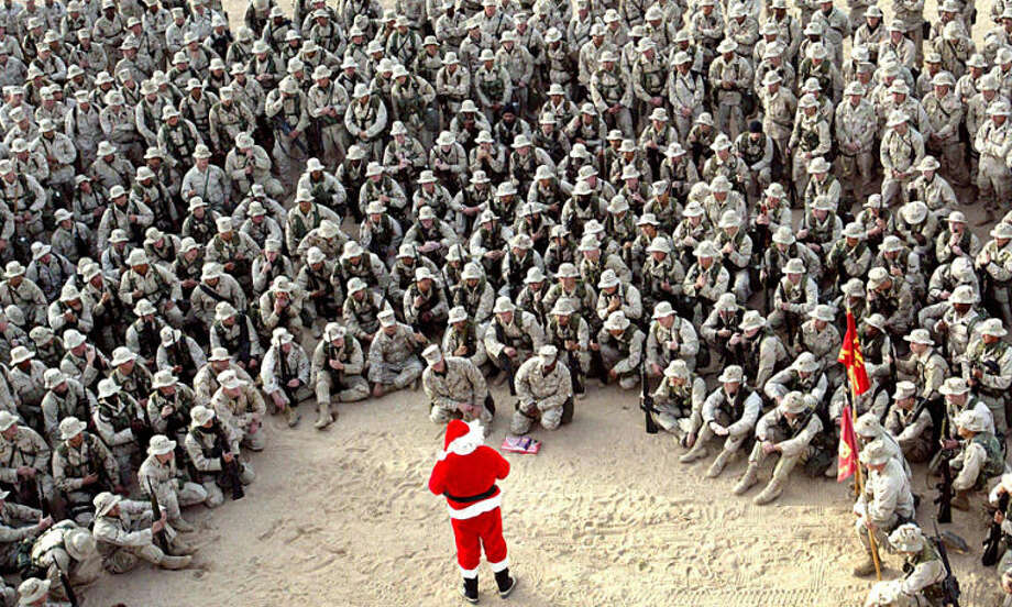 "FILE - In this Tuesday, Dec. 24, 2002 file photo, hundreds of U.S. Marines gather at Camp Commando in the Kuwait desert during a Christmas eve visit by Santa Claus. Anja Niedringhaus, a courageous and immensely talented Associated Press photographer who has covered everything from sports to war, was killed while covering elections in Afghanistan on Friday April 4, 2014. Niedringhaus was in a car in eastern Afghanistan with AP reporter Kathy Gannon when, according to a freelancer who was with them, an Afghan policeman approached them, yelled ""Allahu Akbar"" _ God is Great _ and opened fire on them in the back seat with his AK-47. Niedringhaus was killed instantly and Gannon was wounded. (AP Photo/Anja Niedringhaus, File)"