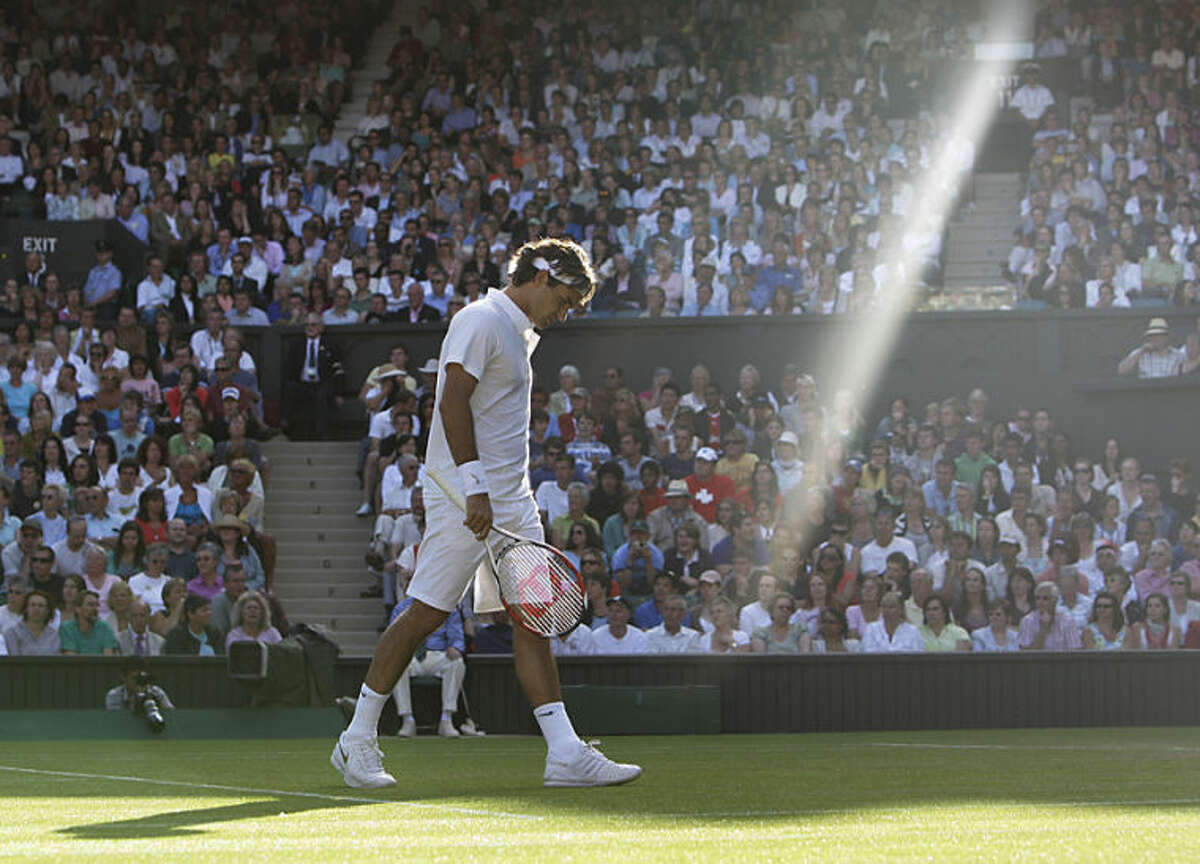 """FILE - In this Wednesday, June 25, 2008 file photo, Switzerland's Roger Federer walks across the court as a shaft of late afternoon light illuminates the Centre Court during his second round match against Sweden's Robin Soderling at Wimbledon, England. Anja Niedringhaus, a courageous and immensely talented Associated Press photographer who has covered everything from sports to war, was killed while covering elections in Afghanistan on Friday April 4, 2014. Niedringhaus was in a car in eastern Afghanistan with AP reporter Kathy Gannon when, according to a freelancer who was with them, an Afghan policeman approached them, yelled """"Allahu Akbar"""" _ God is Great _ and opened fire on them in the back seat with his AK-47. Niedringhaus was killed instantly and Gannon was wounded. (AP Photo/Anja Niedringhaus, File)"""