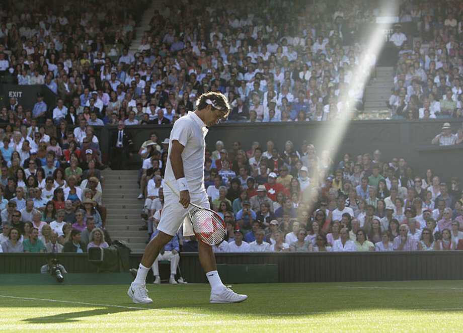 "FILE - In this Wednesday, June 25, 2008 file photo, Switzerland's Roger Federer walks across the court as a shaft of late afternoon light illuminates the Centre Court during his second round match against Sweden's Robin Soderling at Wimbledon, England. Anja Niedringhaus, a courageous and immensely talented Associated Press photographer who has covered everything from sports to war, was killed while covering elections in Afghanistan on Friday April 4, 2014. Niedringhaus was in a car in eastern Afghanistan with AP reporter Kathy Gannon when, according to a freelancer who was with them, an Afghan policeman approached them, yelled ""Allahu Akbar"" _ God is Great _ and opened fire on them in the back seat with his AK-47. Niedringhaus was killed instantly and Gannon was wounded. (AP Photo/Anja Niedringhaus, File)"