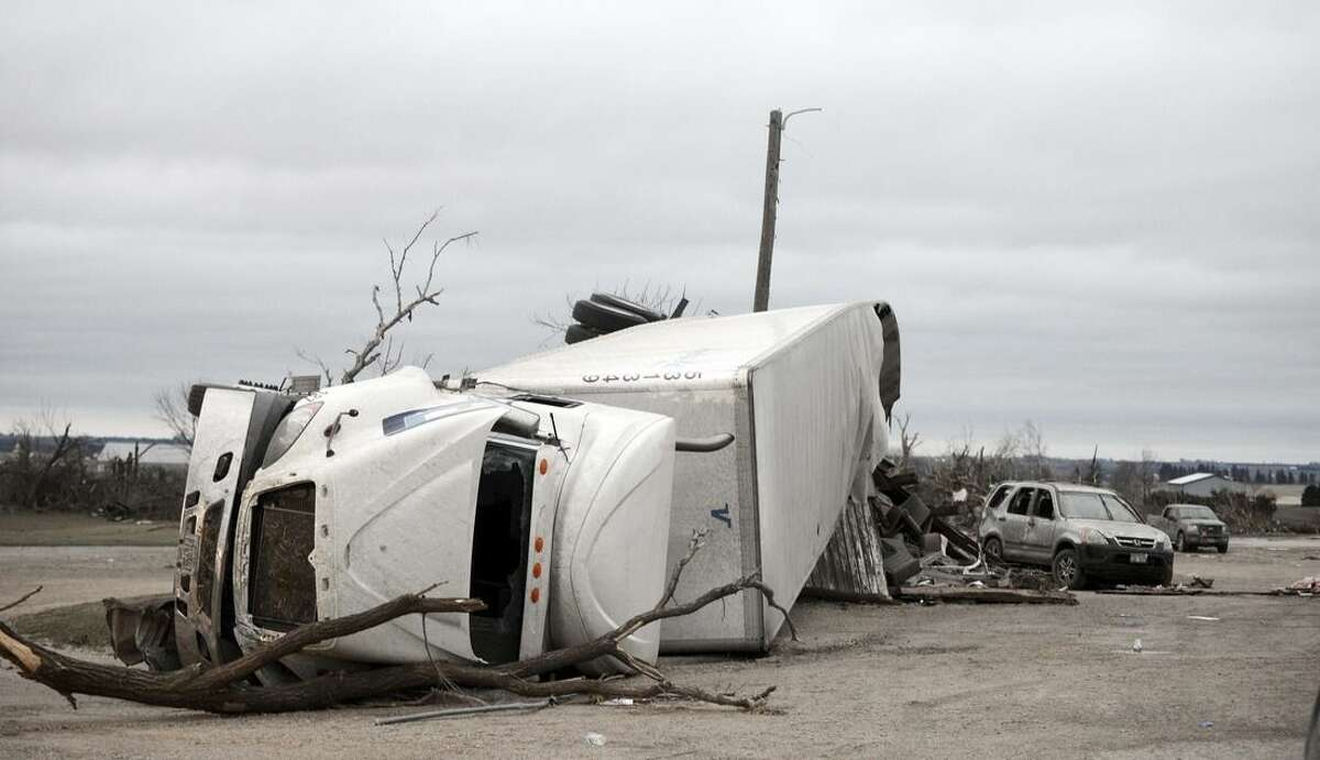 A rolled over semi-trailer sits among debris at Route 64 and 251 in Rochelle, Ill., Friday, April 10, 2015, after a tornado past through the area Thursday evening. The National Weather Service says at least two tornadoes churned through six north-central Illinois counties Thursday night. One person was killed in the small town of Fairdale, Ill. (AP Photo/Daily Herald, Paul Michna) MANDATORY CREDIT, MAGS OUT